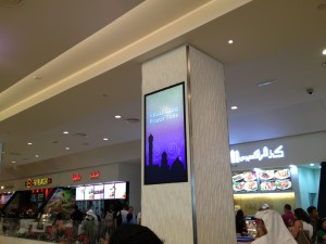 Call to prayer broadcast on slides and over loudspeakers in big, modern, US-style mall (this is the food court)